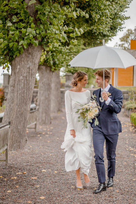 Bride and groom walking under an umbrella during the portraitsession.