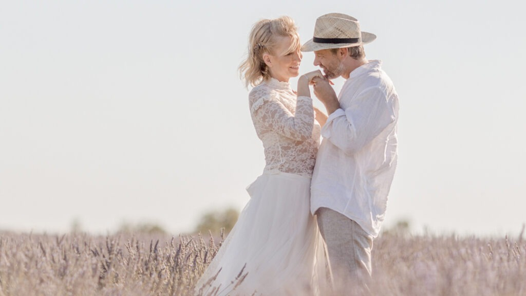 Couple standing in a lavenderfield in Provence and he is kissing her hand