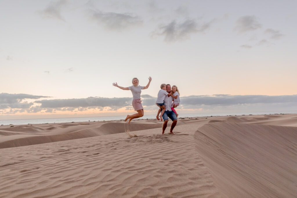 jumping family in maspalomas Gran canary during sunrise
