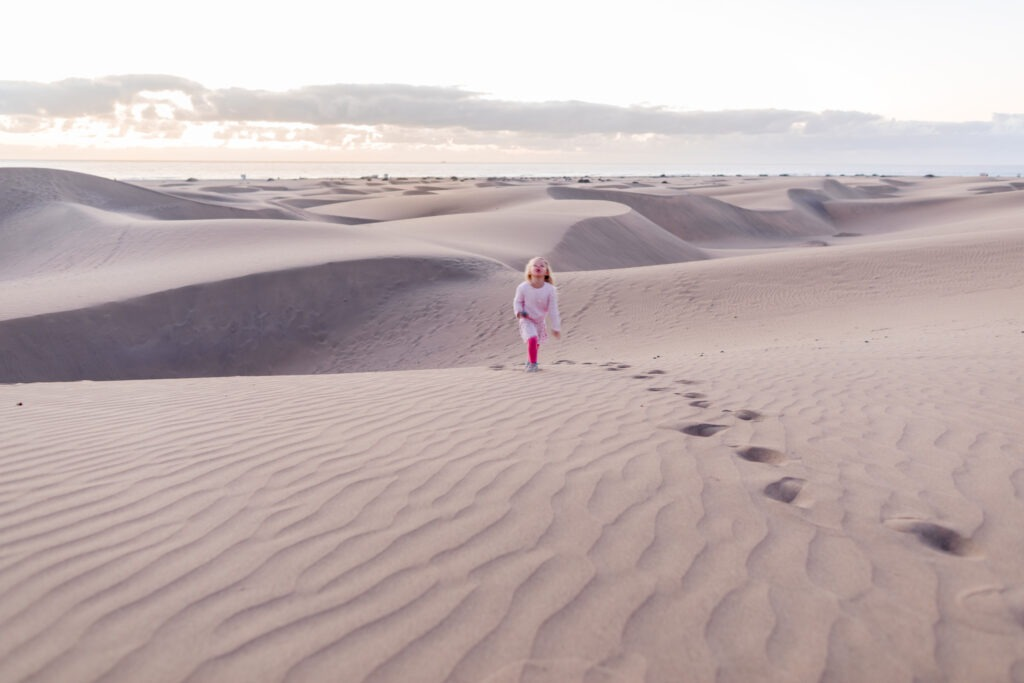 Girl bringing a stone up a sand dune in Maspalomas sunrise