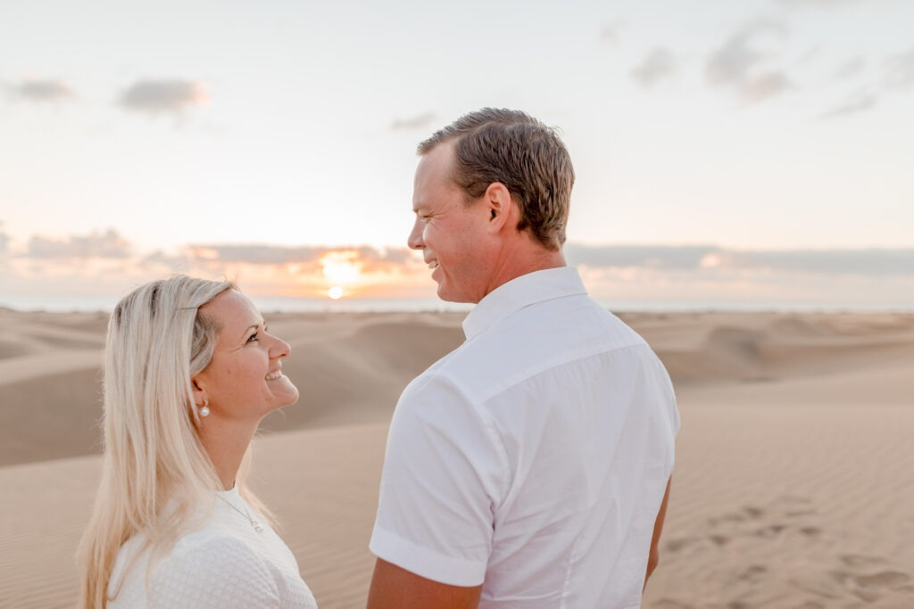 Couple looking at each other with the sunrise in front of them in Maspalomas. Gran canary