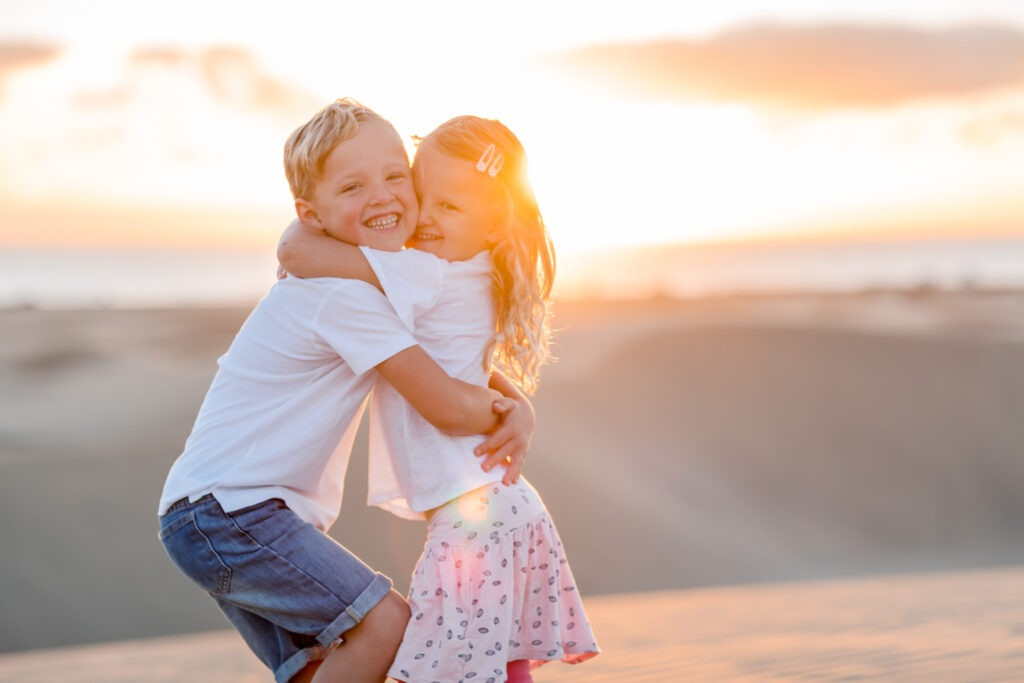 Two kids hugging in sunrise Maspaloma