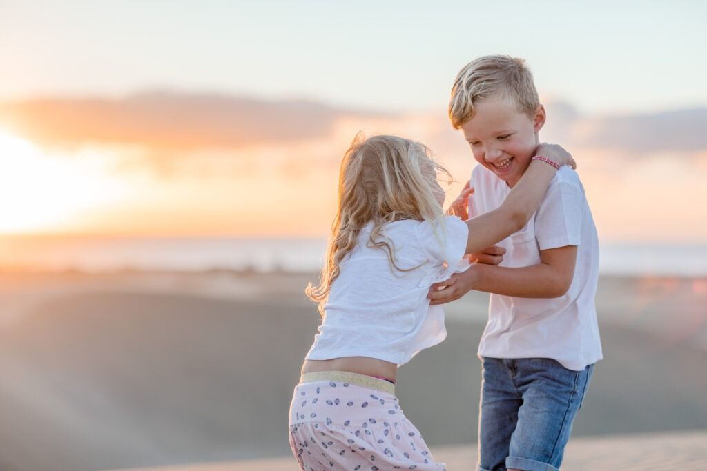 Two kids tickeling in sunrise sanddunes