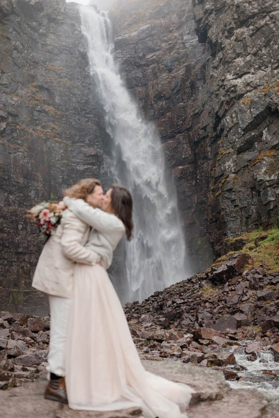 A couple is kissing and hugging closely with a big waterfall behind them