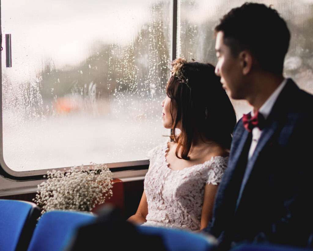 deal with it, rainy forcast bride and groom looking out the window on a boat