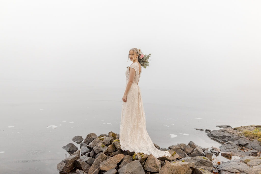 A bride is standing on the rooks overlooking the misty sea