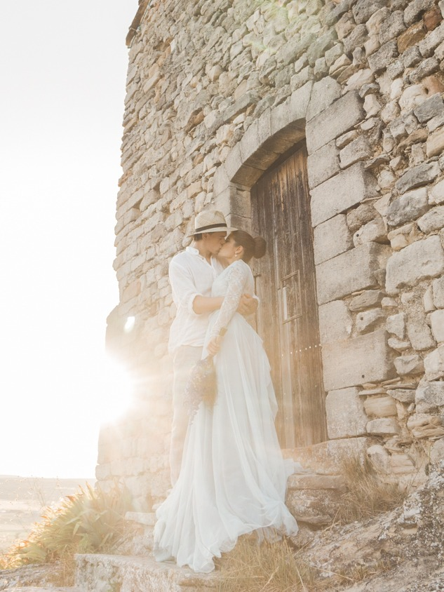 Bride and groom standing on a stone stair kissing in the backlight of a sunset