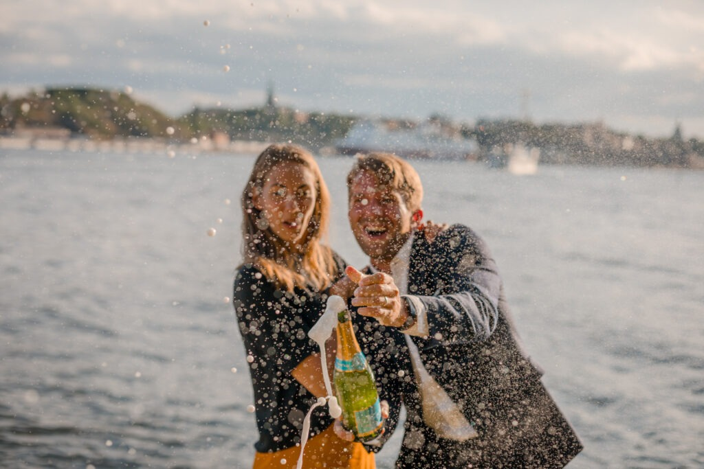 A couple spraying champagne in Stockholm