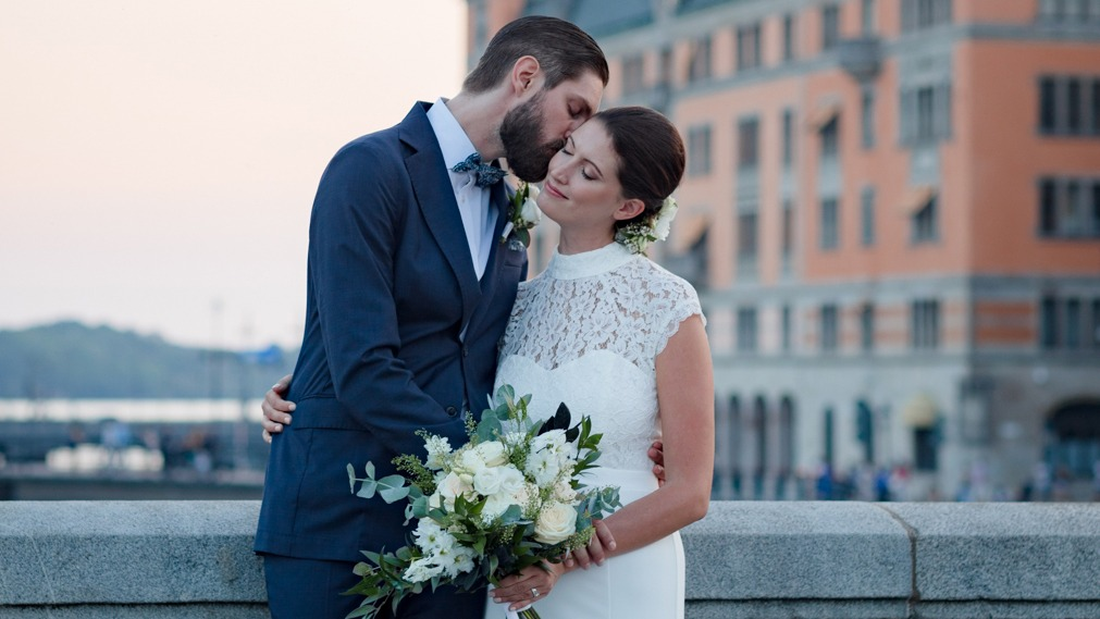 Groom leaning to kiss his bride on the cheek by a bridge in Stockholm