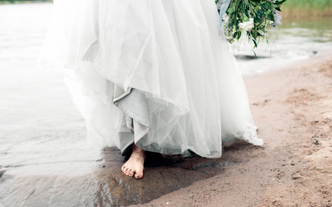 A barefoot bride is walking up from the water in a light blue dress