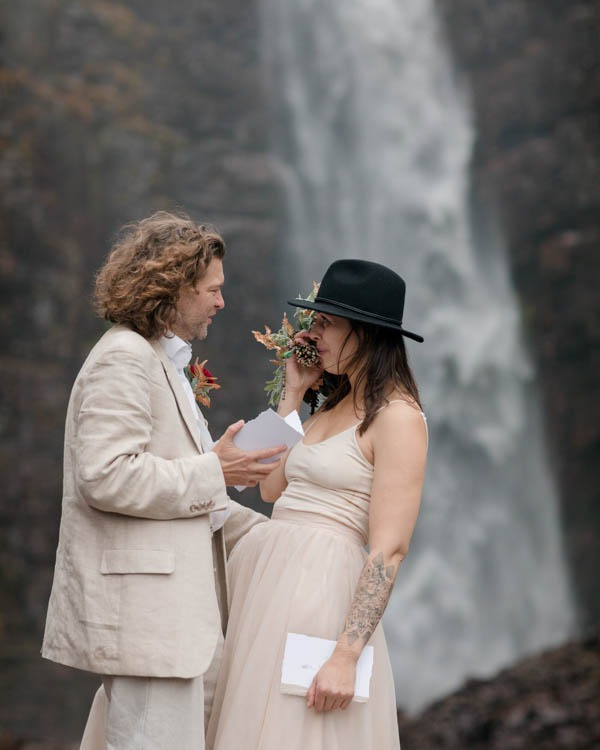 A couple standing with a waterfall behoind them, he is reading his vows, she is crying