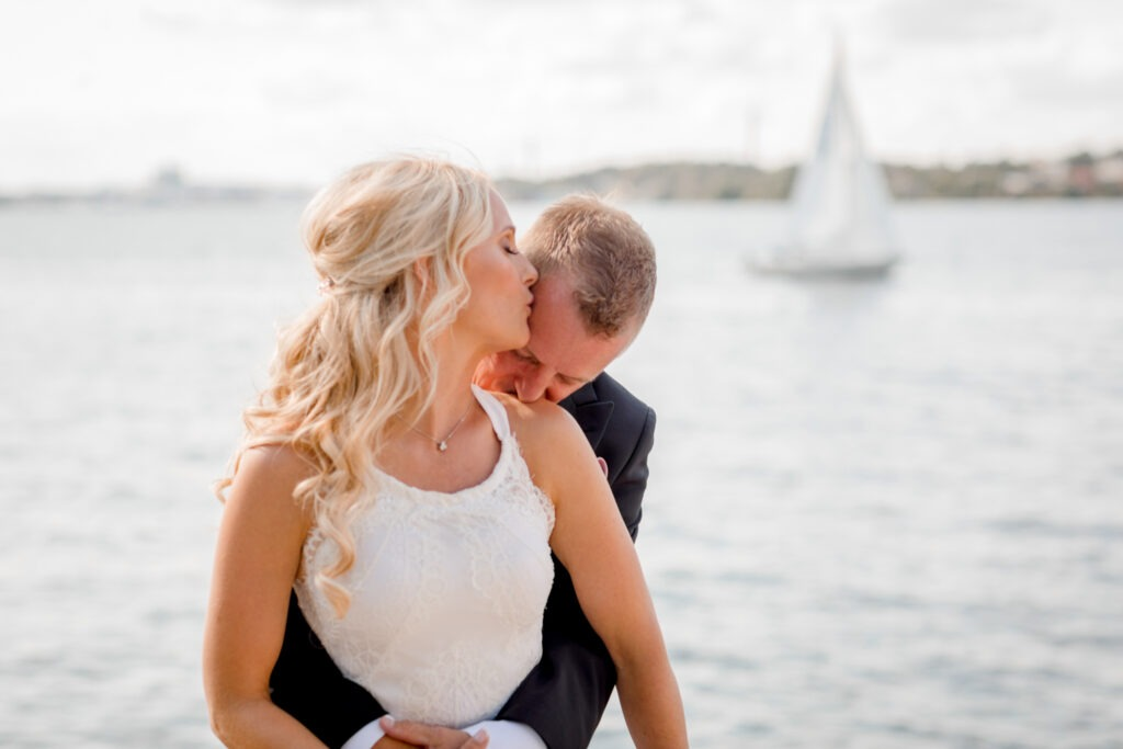 Groom standing behind his bride kissing her shoulder as a sailing boat is passing behind them