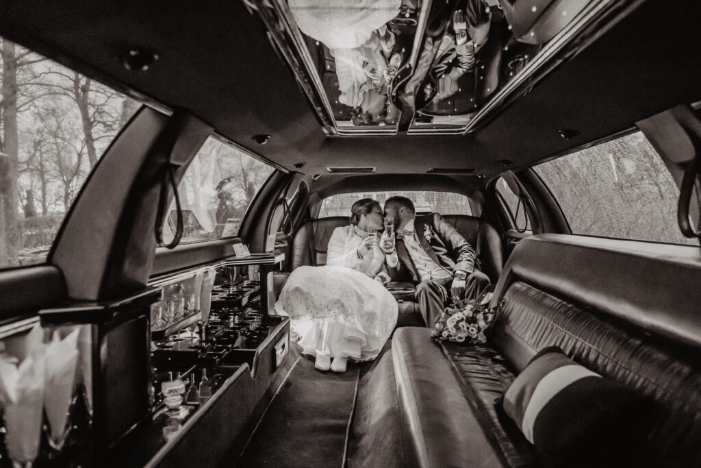 A newlywed in a limousine kissing with a champagne glass in their hands