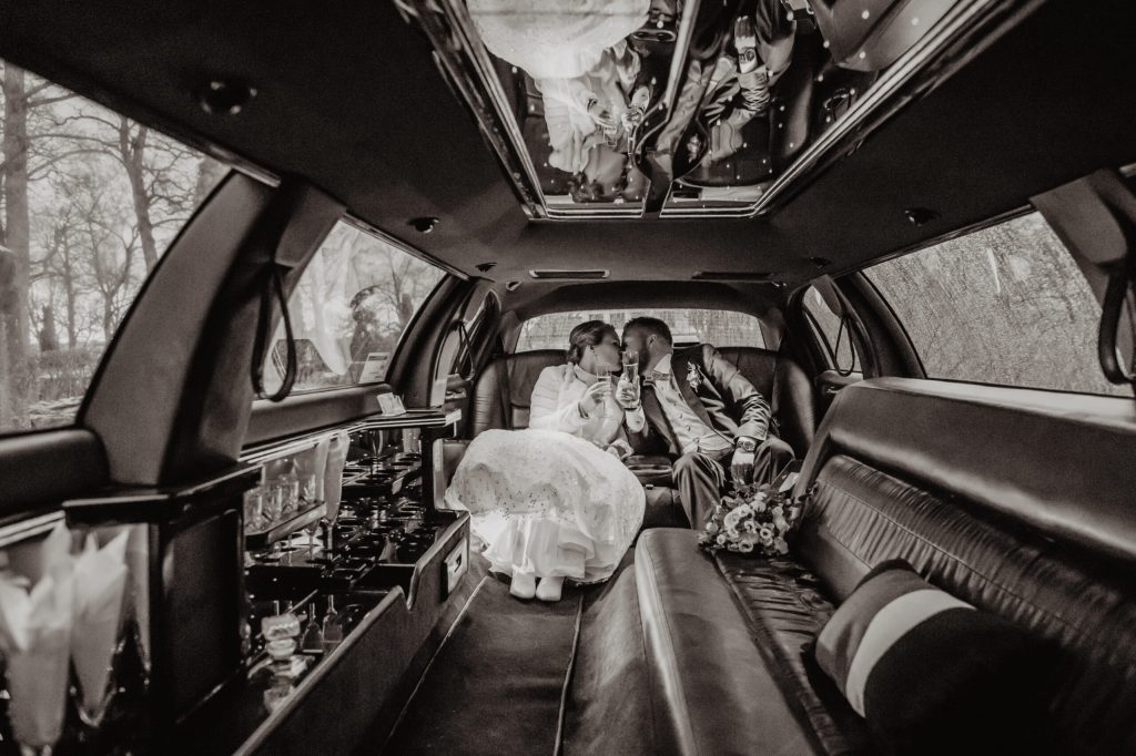 narrow down your guest list, newlyweds in a limousine kissing with a champagne glass in their hands