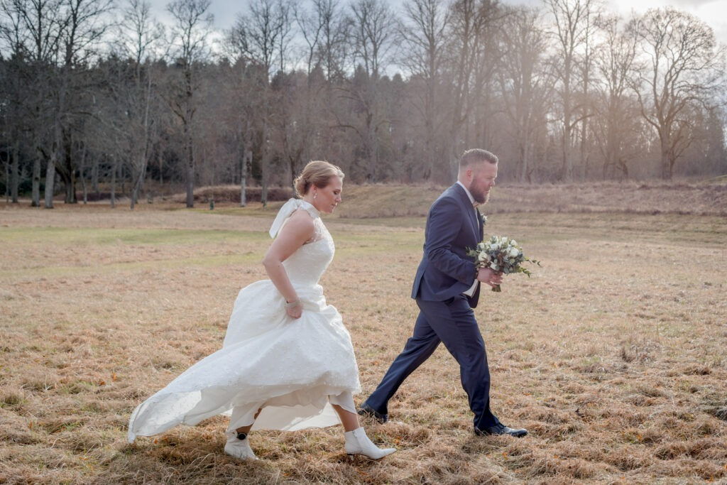 Bride and groom hurrying over a field in february cold