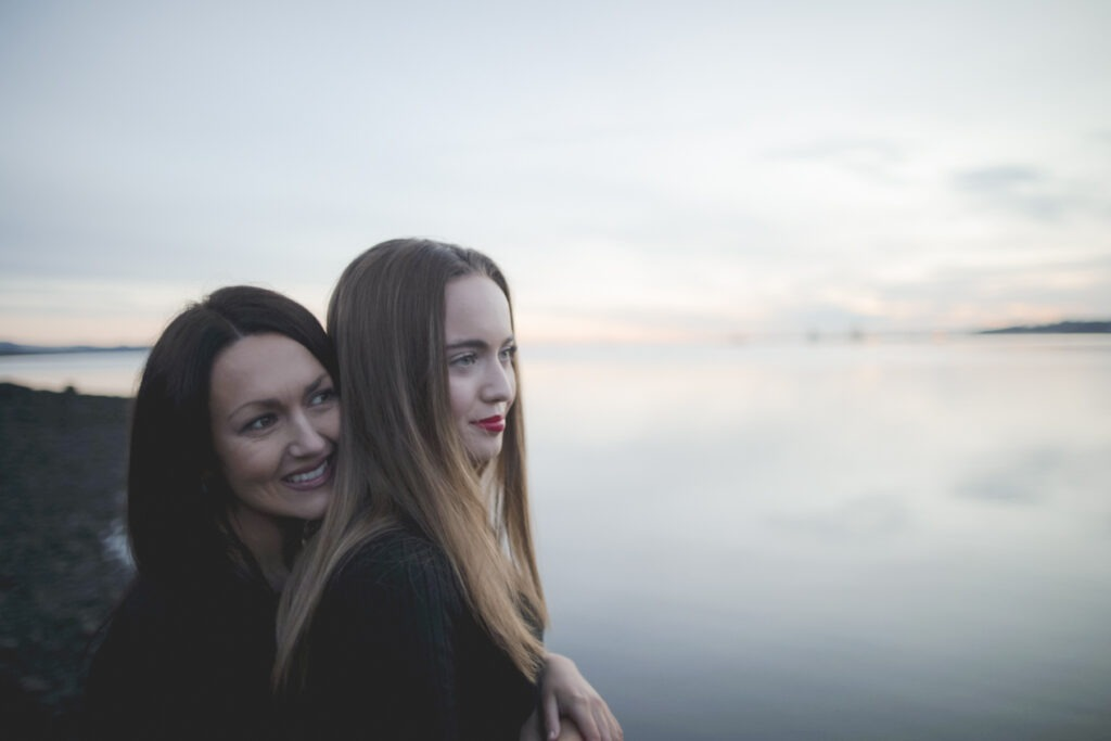 Mom and daughter standing by the shore of Edinburgh lauging and looking a head