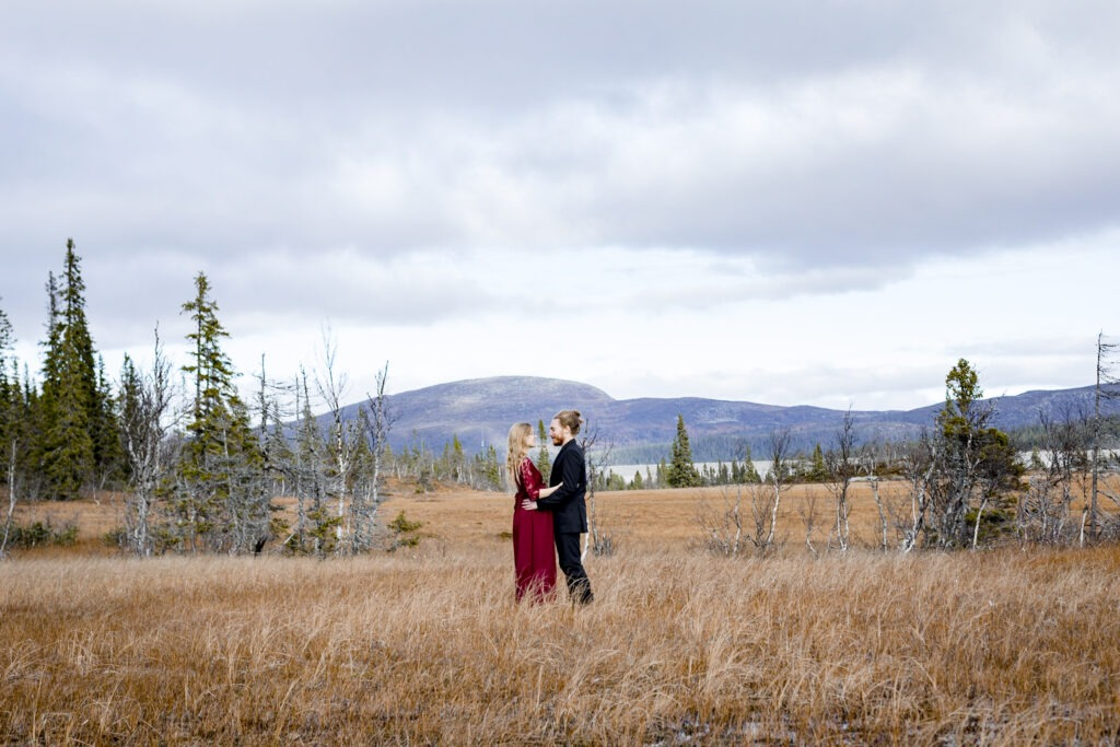 Couple standing facing each other in teh wild with mountain backround