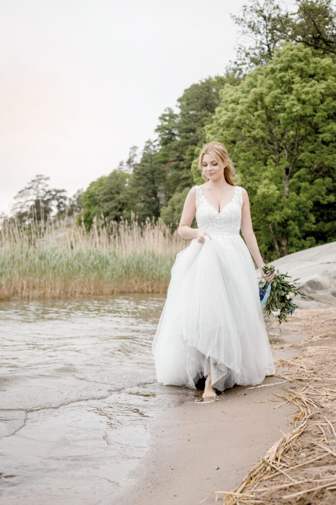 A bride walking barefoot by the shore in a blue weddingdress