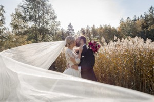October wedding with a veil flying in the wind as the couple kiss