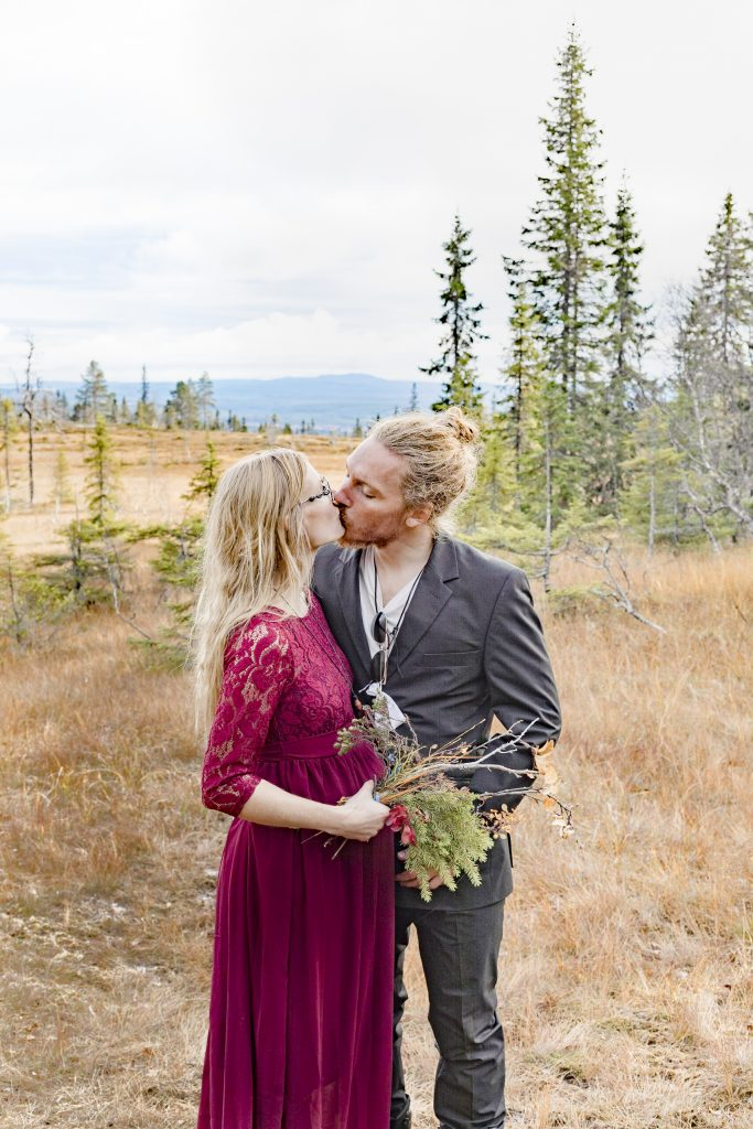 sweet kiss between bride and groom in the forest
