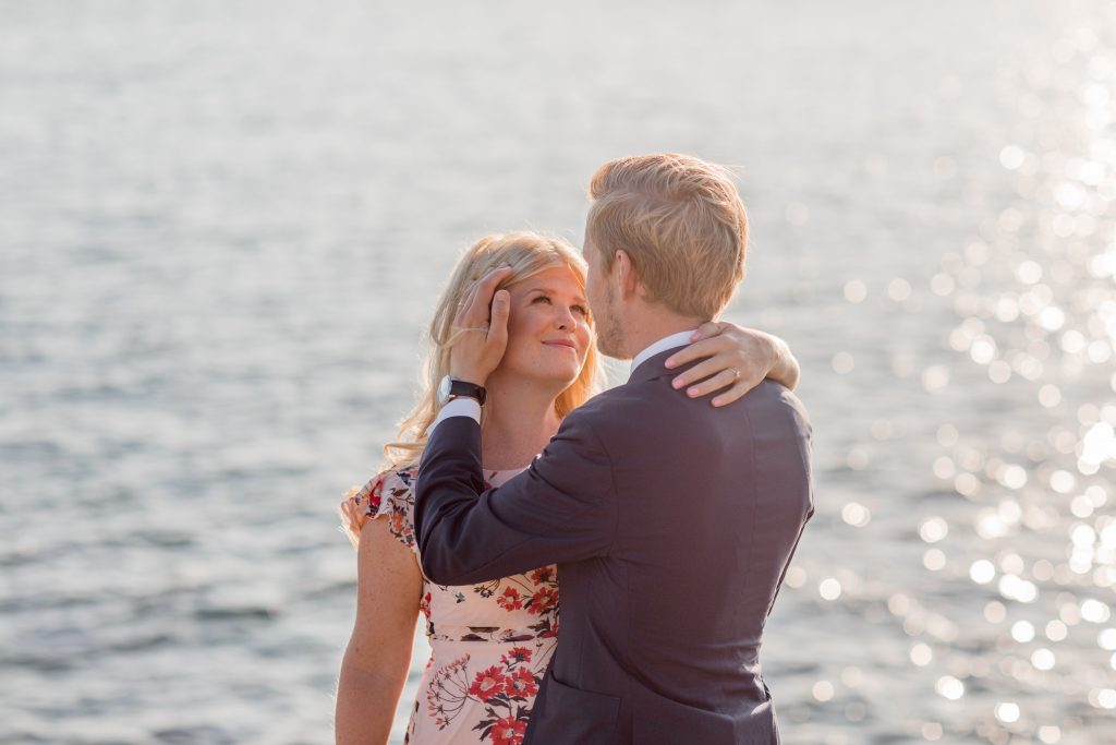 A couple standing on the cliffs of Fjäderholmarna and the guy is caressing her cheek
