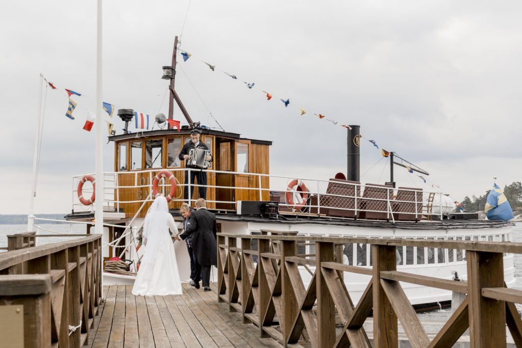 A wedding couple entering a boat