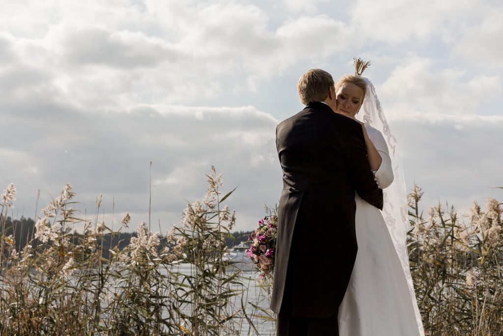 A groom kissing his bride by the shore in dramatic skies