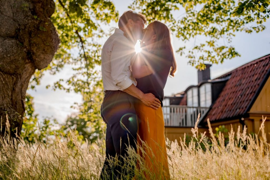 A couple kissing in back light under a tree