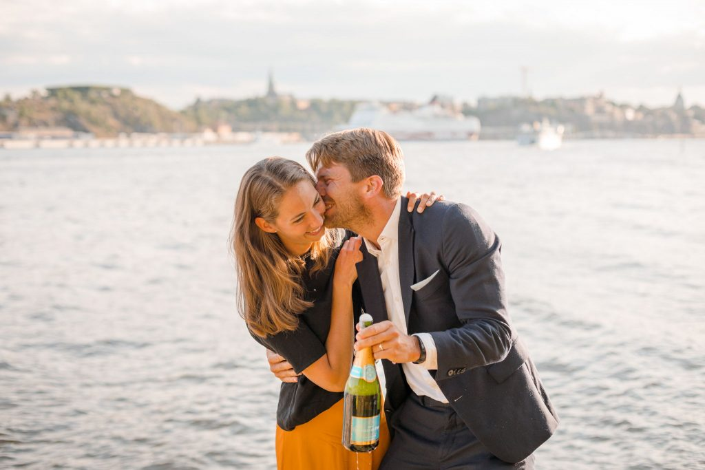 Couple having fun after popping a champagne bottle