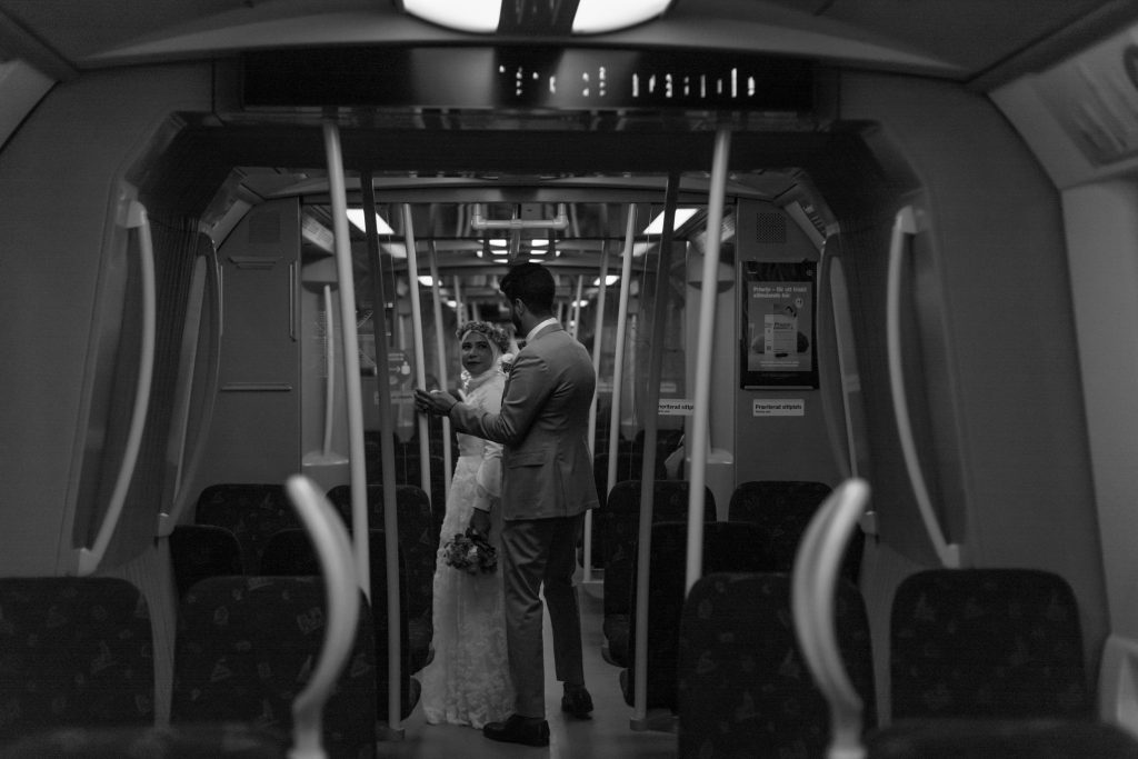 A elopement couple standing in a subway getting ready to step off.