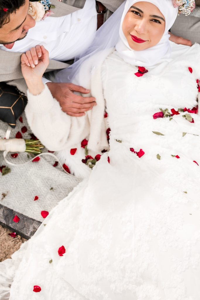On the beach in this urban elopement lying down the bride has gotten dried rose pedals over her