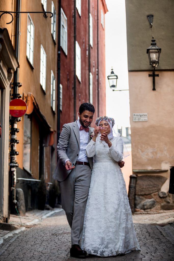 A wedding couple sharing a cone of icecream in Stockholm city old town