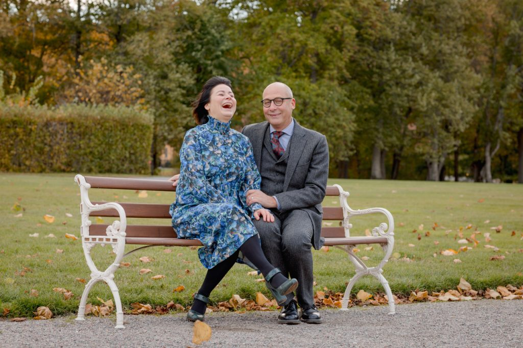 Couple ona. bench in the wind lalughing