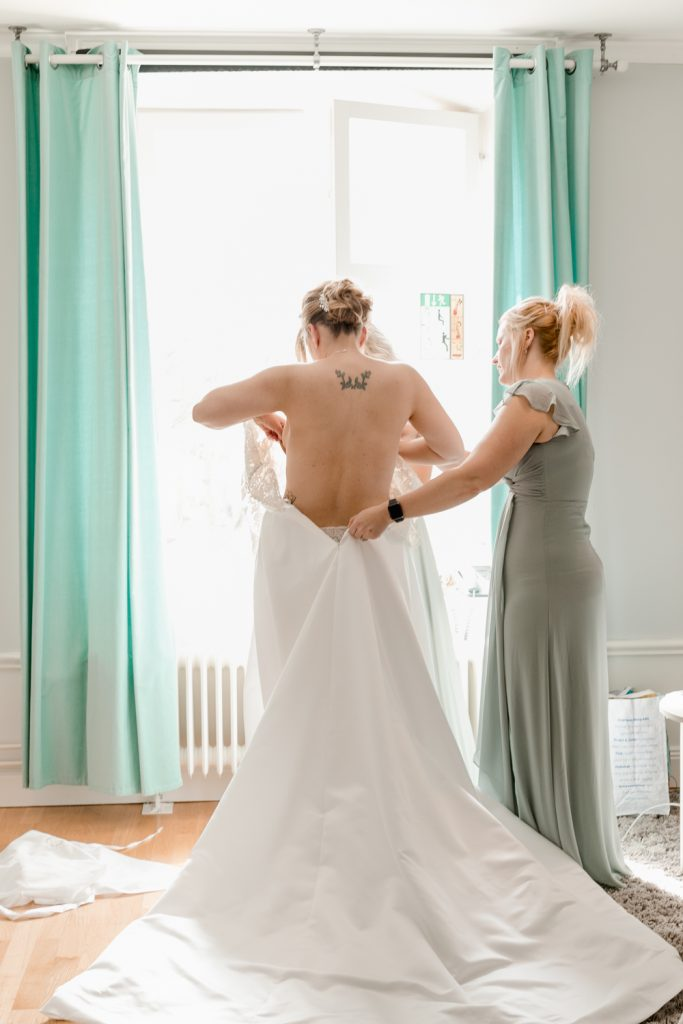 narrow down your guest list and the bride getting her dress on with 2 bridesmaids