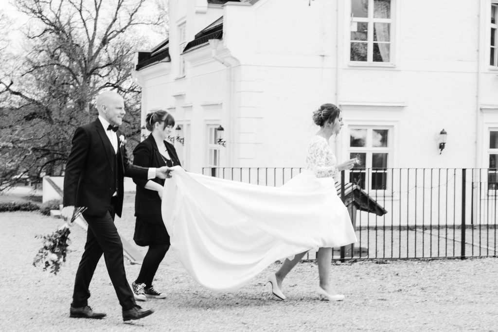 posing, a bride getting help with her dress walking