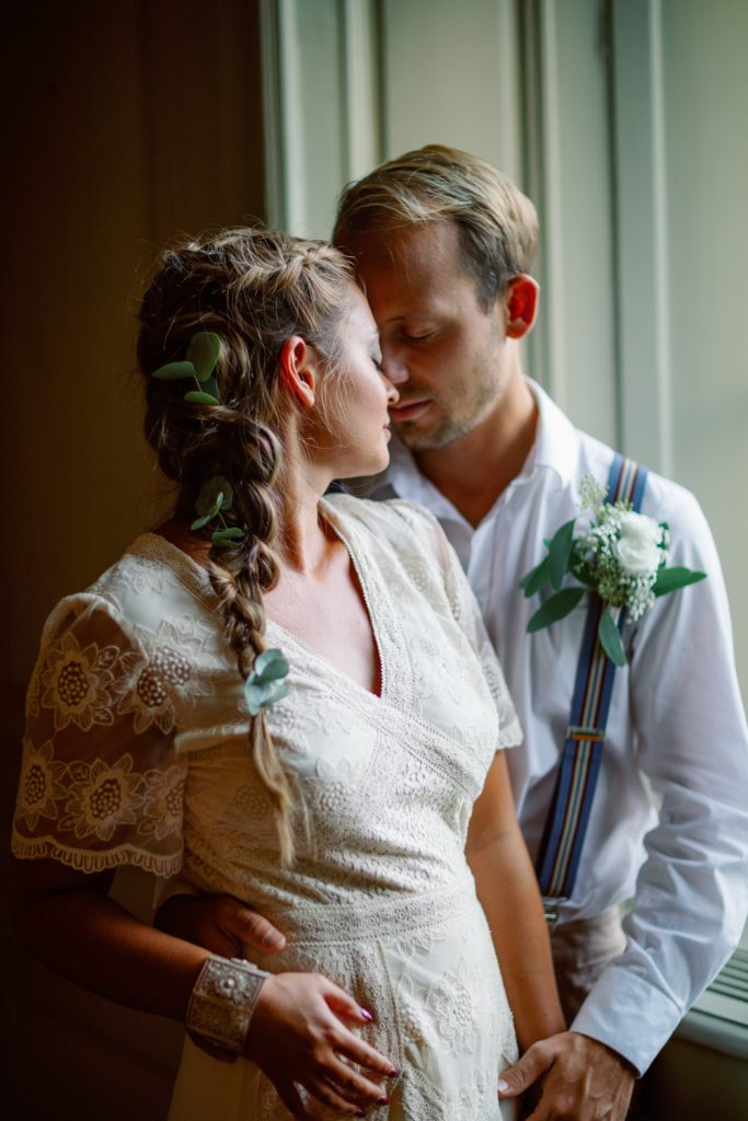 bridal hairdo's and a couple standing in a window forehead against forehead