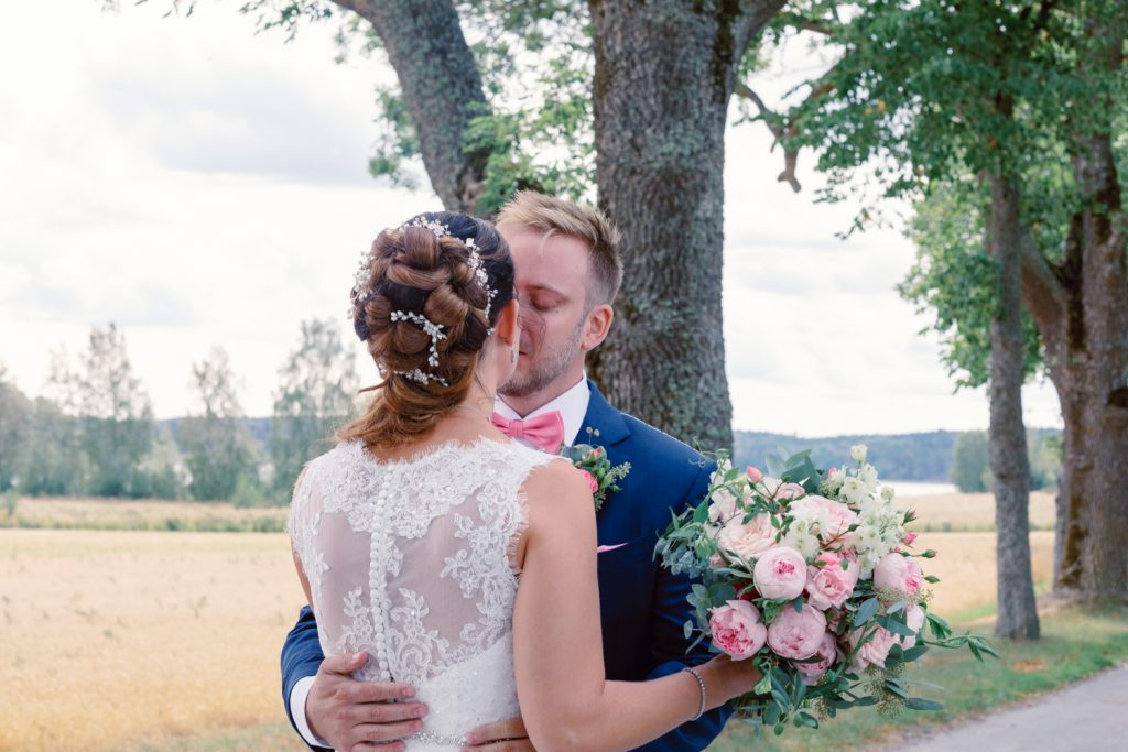 bridal hairdo's where groom is kissing his bride to be after first look
