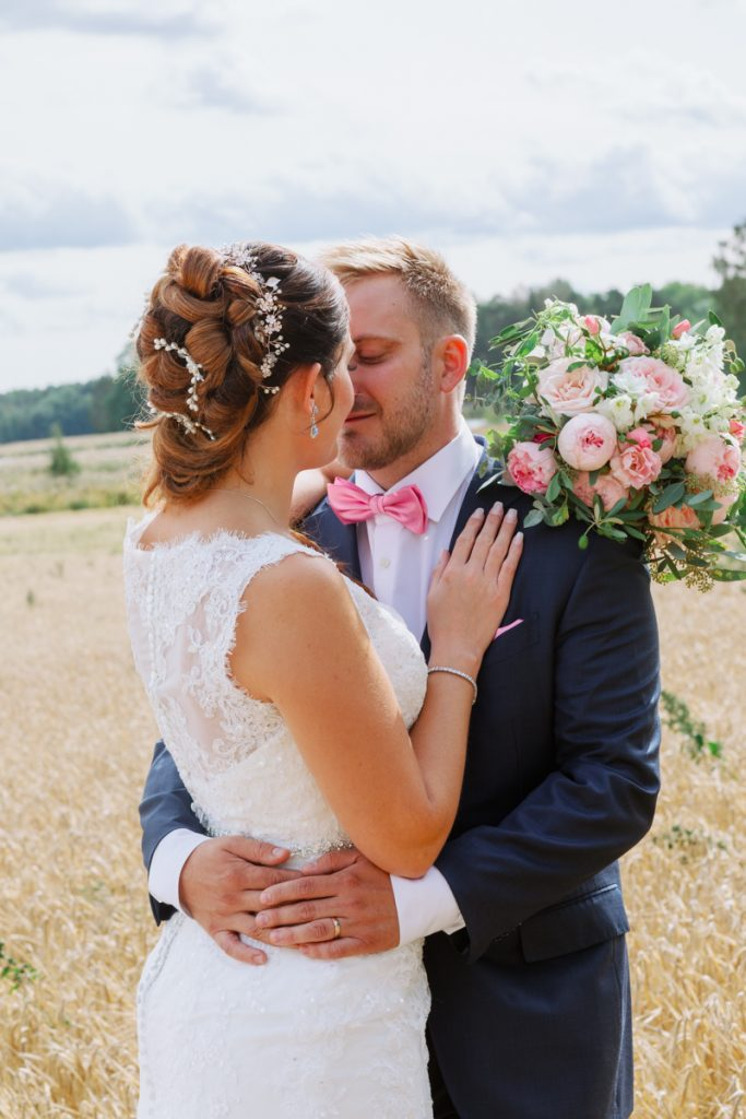 bridal hairdo's when a couple is standing in a wheat field and kiss