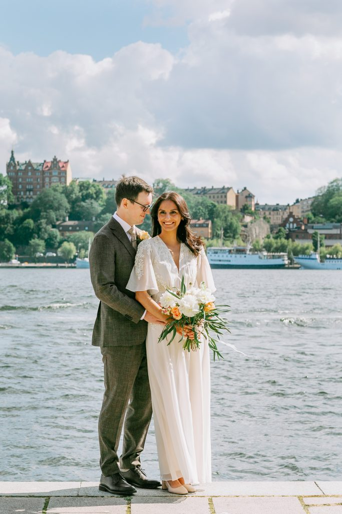summer elopement an a beautiful backdrop of Stockholm water. Bride looking into the camera and the groom leaning against her
