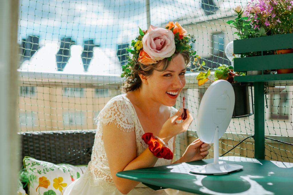 adventure elopement bride putting on lipstick on the balcony