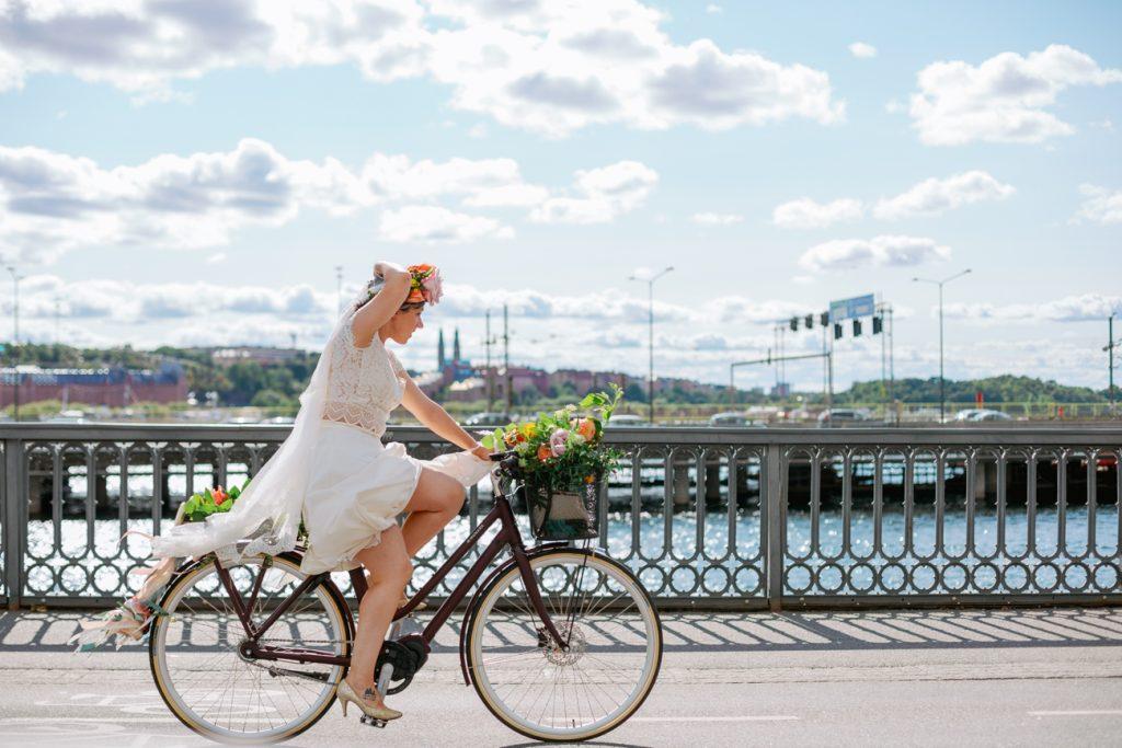 adventure elopement bride on bike towards Stockholm cityhall