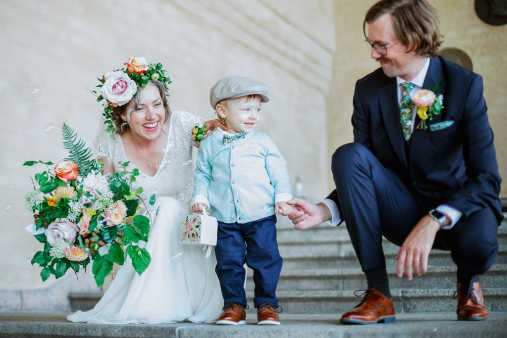 adventure elopement bride and groom with kid greeted by family outside Stockholm cityhall