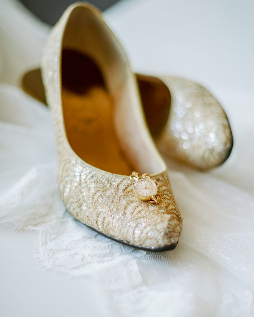 adventure elopement vintage golden shoes and a certina watch on the lace veil
