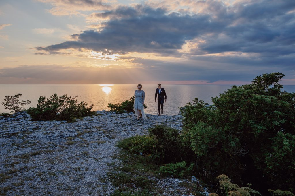 beautiful and unforgettable elopement wedding couple walking on a cliff in sunset Gotland