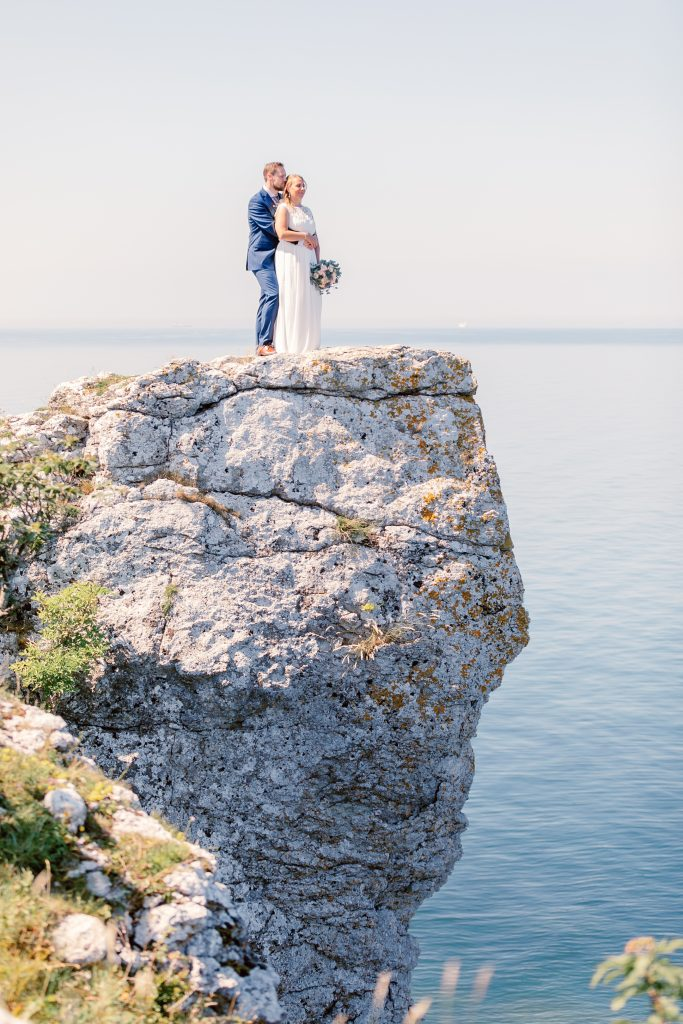 important lessons bride and groom standing on a cliff overlooking the ocean
