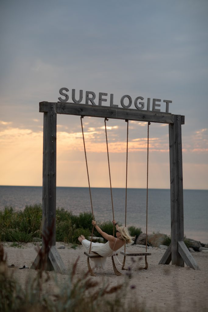 important lessons a girl swinging and a sunset backdrop at Surflogiet, Gotland