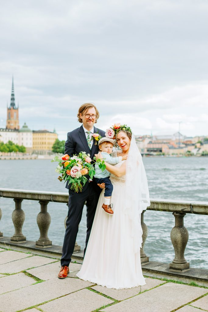 adventure elopement couple and toddler standing. by the water with Stockholm in the backround