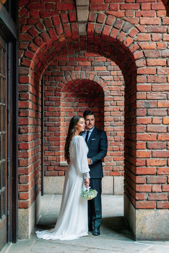 elopement wedding bride and groom standing under arches at city hall looking into the horizon