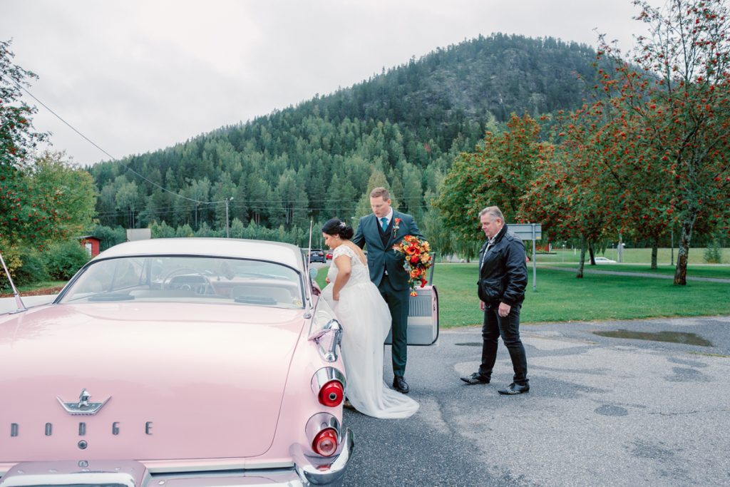 elopement wedding bride getting into a pink dodge