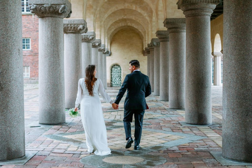 elopement wedding at cityhall couple holding hands talking to each other as they walk away